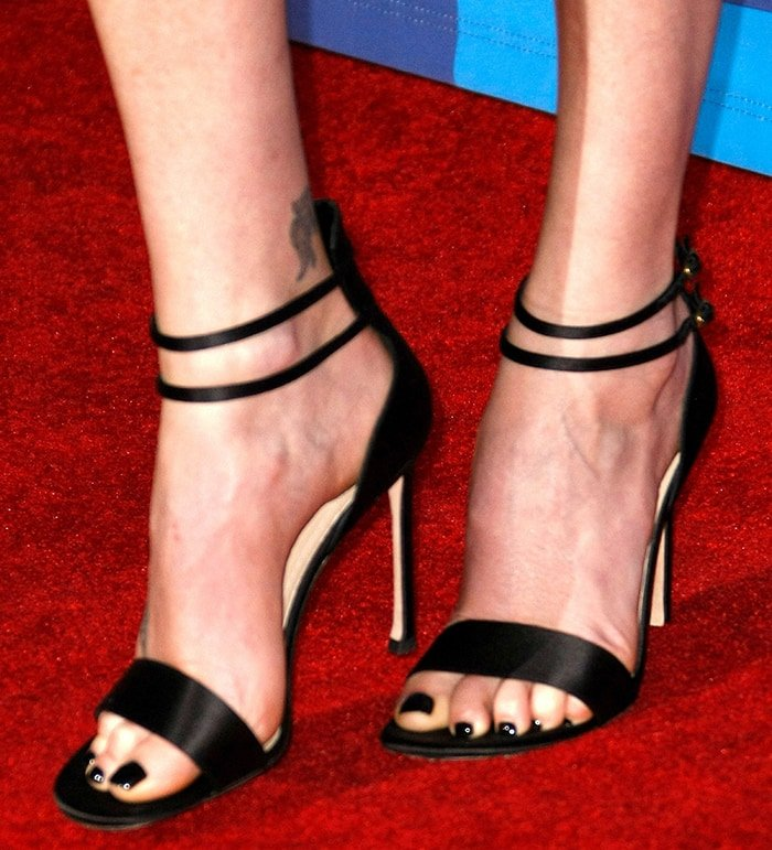 Charlize Theron shows off her feet in black satin sandals