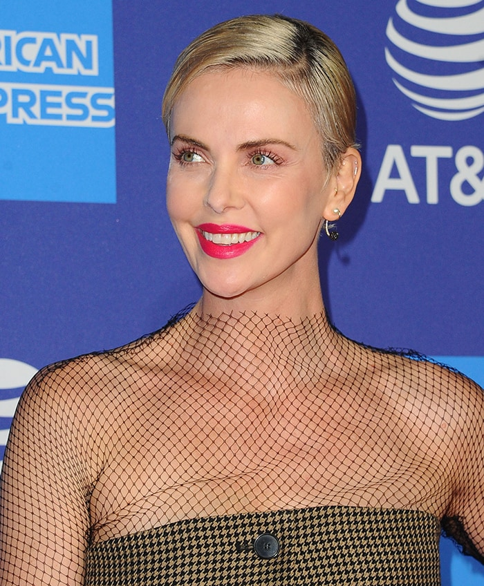 Charlize Theron wears a slicked side-parted pixie hairstyle with pink lipstick