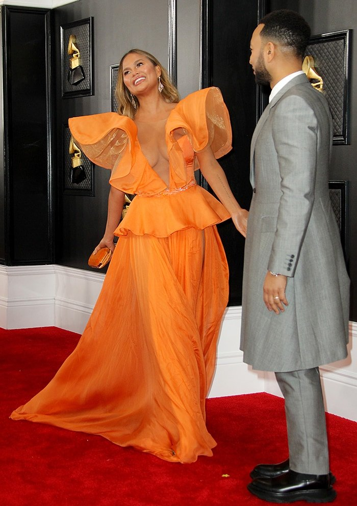 Chrissy Teigen and John Legend smile for photographers on the red carpet