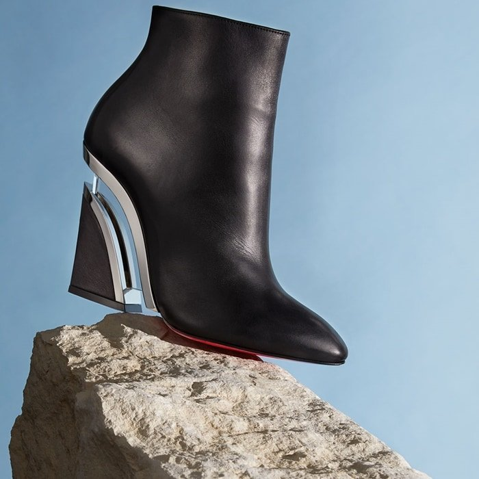 A transparent center bar at the wedge heel and gilt trim create a extraordinary floating effect on an almond-toe bootie crafted from supple calfskin