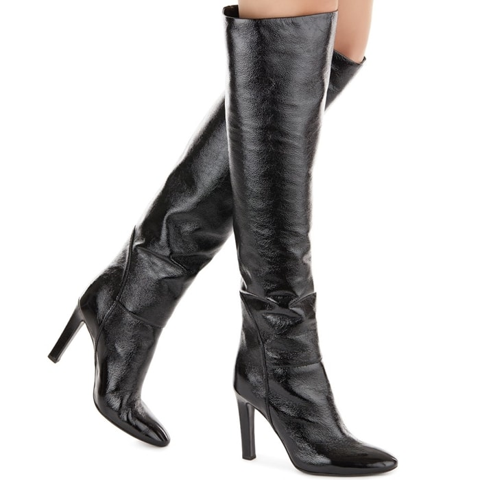 These knee-high, laminated silver leather boots feature high heels and are set on a leather sole with logo