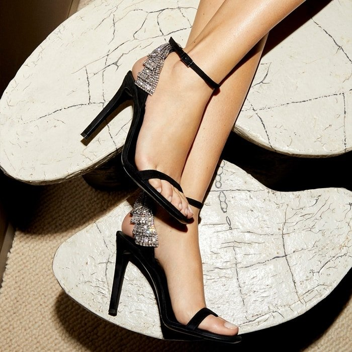 These high-heel, black suede Jamila sandals are embellished by the vintage Bow jewel on the ankle strap