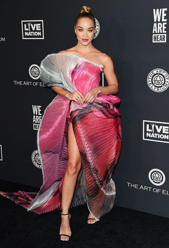 Jasmine Sanders turns heads in a leg-baring Maison Met ombre plisse gown