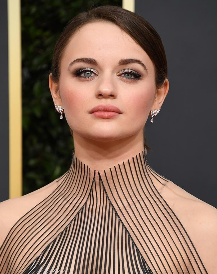 Joey King wears a chic updo with smoky eye-makeup and nude rose lipstick