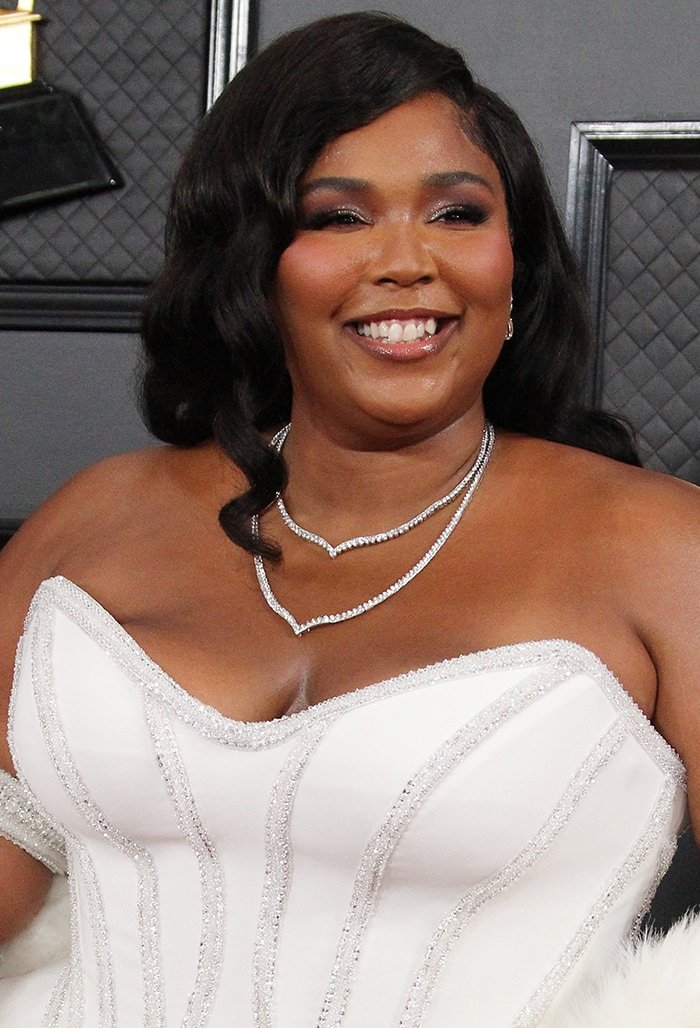 Lizzo wears vintages curls with purple smoky eyeshadow and false eyelashes