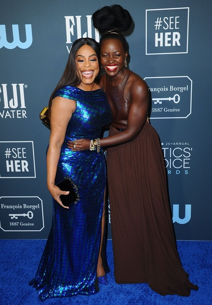Lupita Nyong'o sharing a laugh with Niecy Nash at the 2020 Critics' Choice Awards