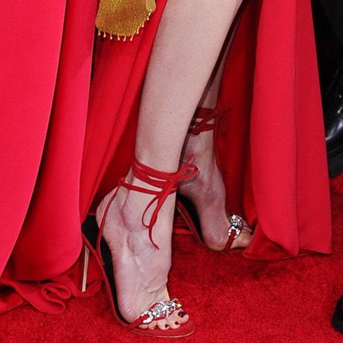 Nicole Kidman's feet in red leather and suede Thais 105mm ankle-wrap sandals from Giuseppe Zanotti featuring an almond toe, a toe strap, crystal embellishments, a branded insole, an ankle strap, and a high stiletto heel