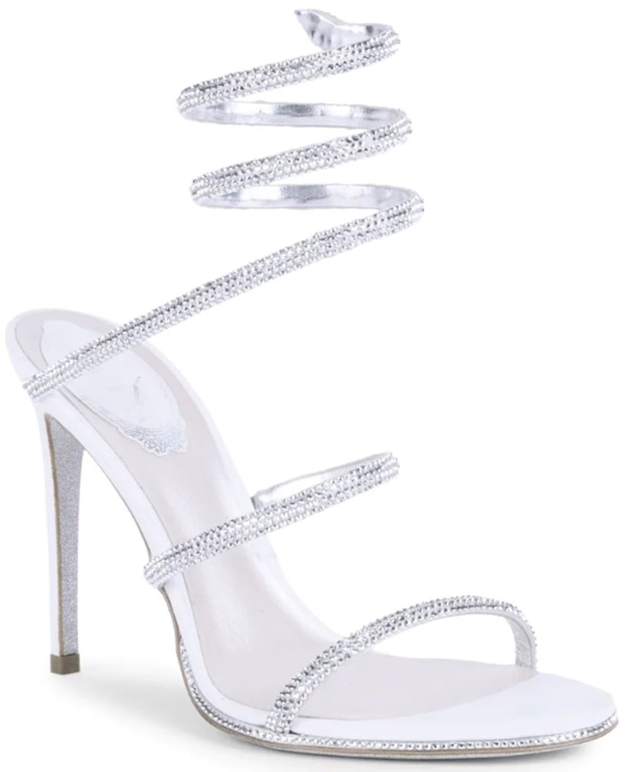 Delicate stiletto sandals rendered in luxe satin are embellished with dazzling crystals in a tonal finish