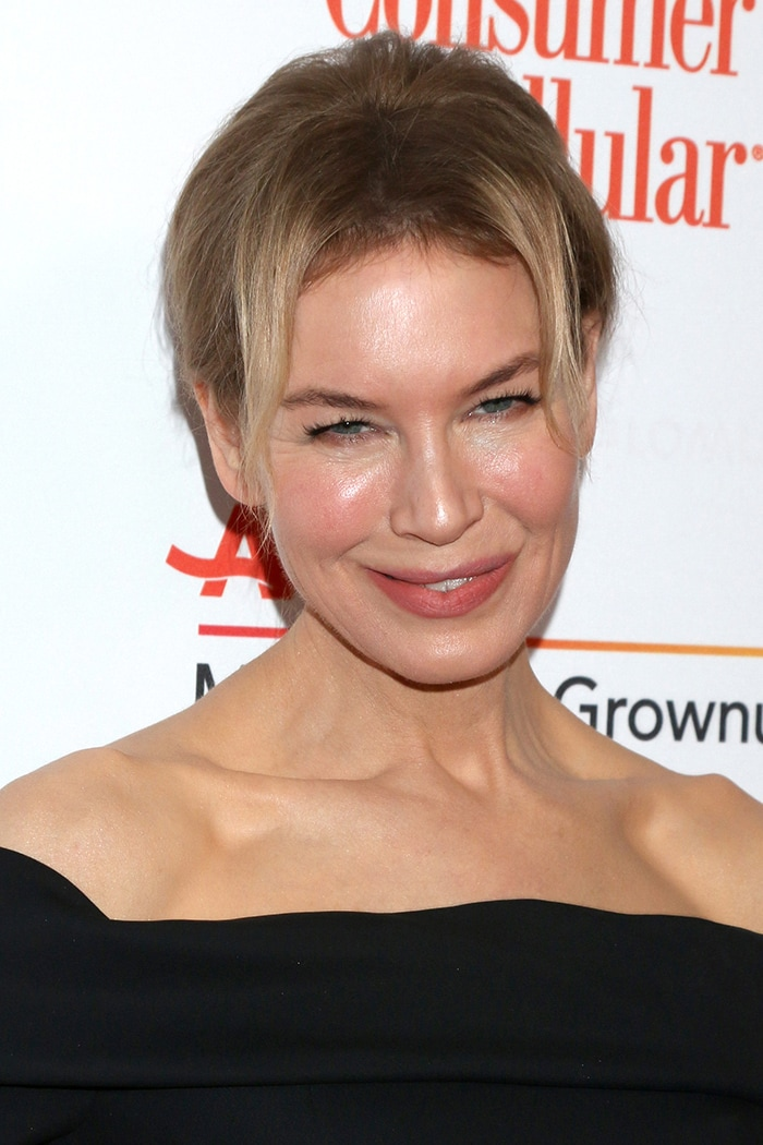 Renee Zellweger pulls her hair up in a chic bun and wears rosy lipstick and blush