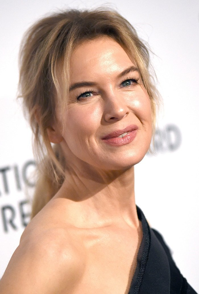 Renee Zellweger wears a messy ponytail with mascara, eyeliner, and pink lipstick