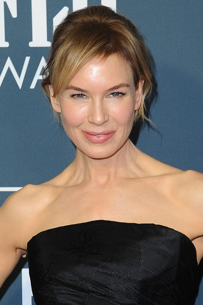 Renee Zellweger wears a chic, messy ponytail with soft pink makeup
