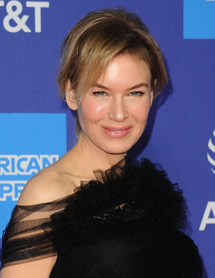 Renee Zellweger wears a loose ponytail with soft pink makeup