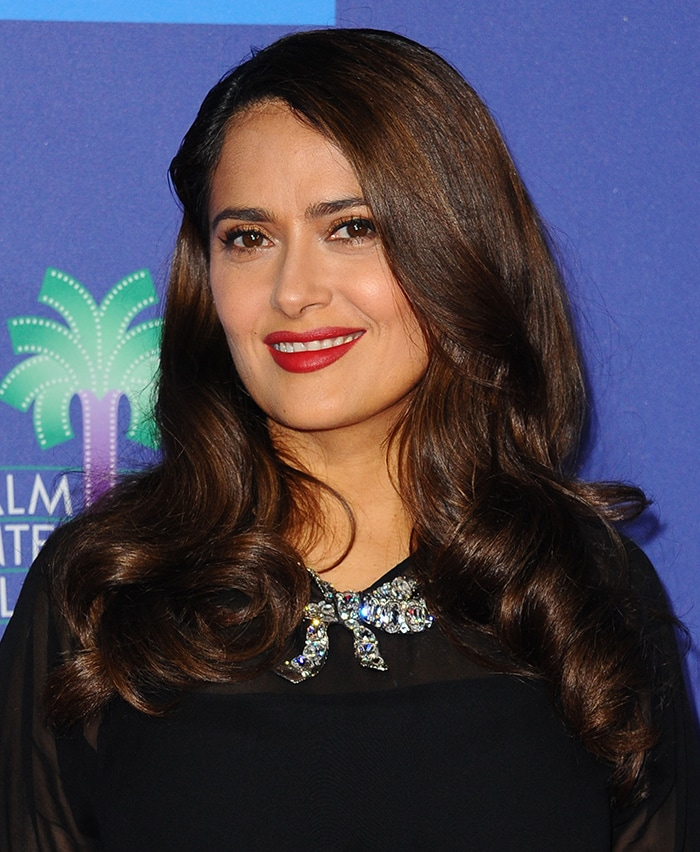 Salma Hayek styles her hair in soft waves and gives her outfit a pop of color with red lipstick