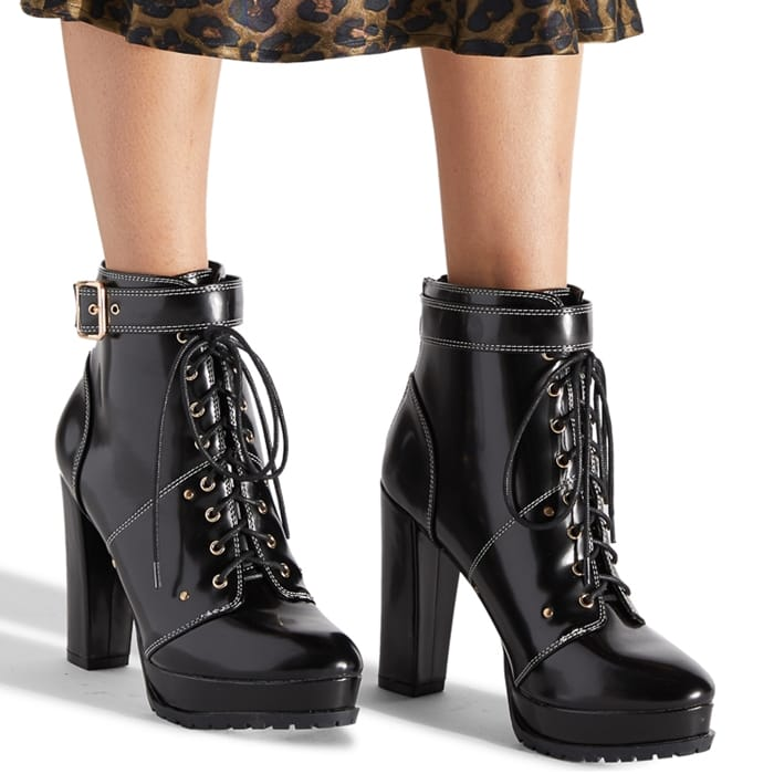 A platform hiker bootie featuring a high block heel, decorative buckle strap, and adjustable laces