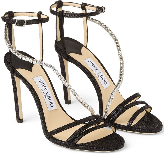 Delicate stiletto sandals featuring a languid, crystal-embellished strap that curves over the foot