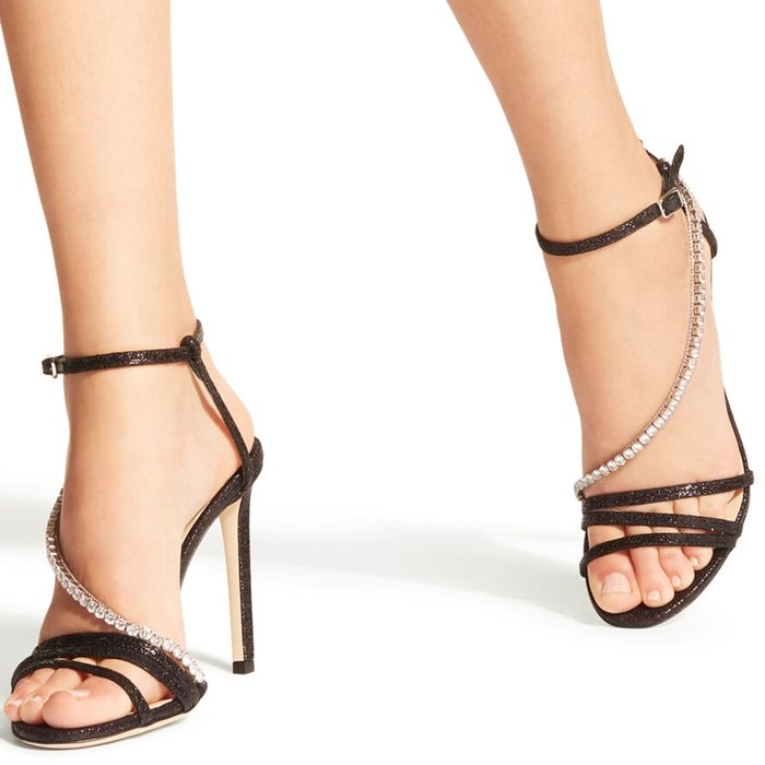 A crystal-embellished chain curves around the foot, adding extra slink and shine to a metallic pink ankle-strap sandal lifted by a stiletto heel