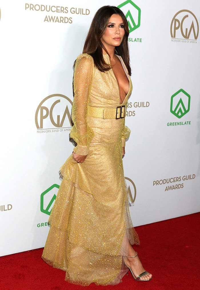 Eva Longoria shows off a buxom display in aTeresa Helbig gold gown with a plunging neckline and jewel embellishments