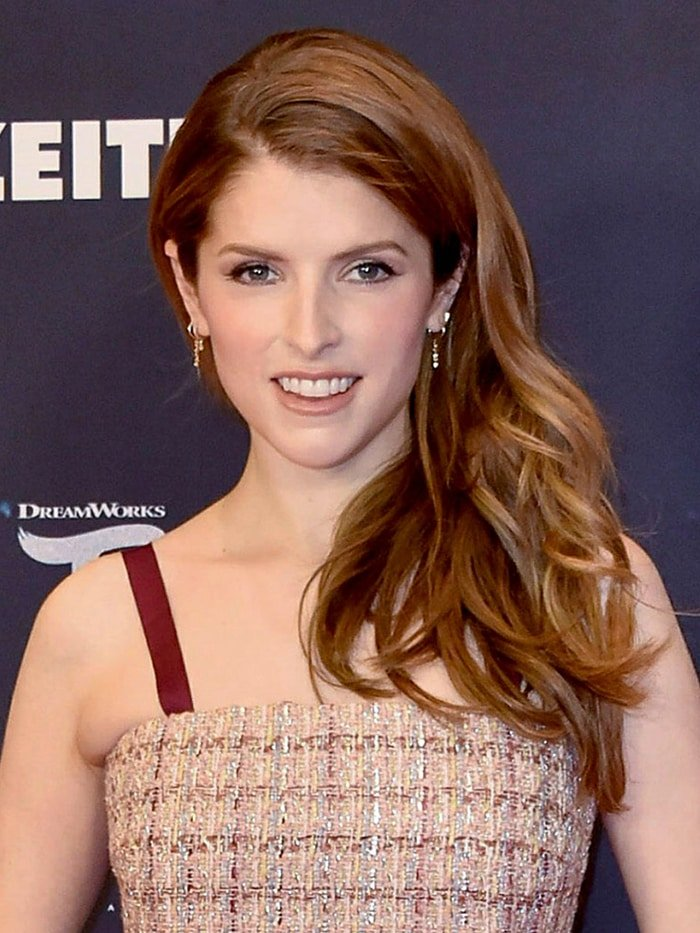 Anna Kendrick wears neutral makeup with her hair cascading over her shoulder in loose waves
