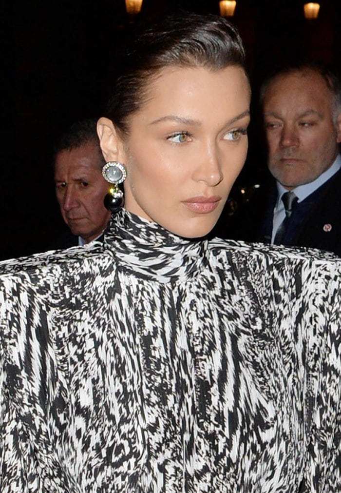 Bella Hadid wears a slicked-back hairstyle with neutral makeup
