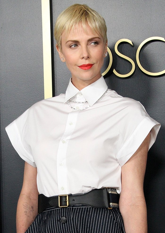 Charlize Theron adds a swipe of bold red lipstick to her monochrome look