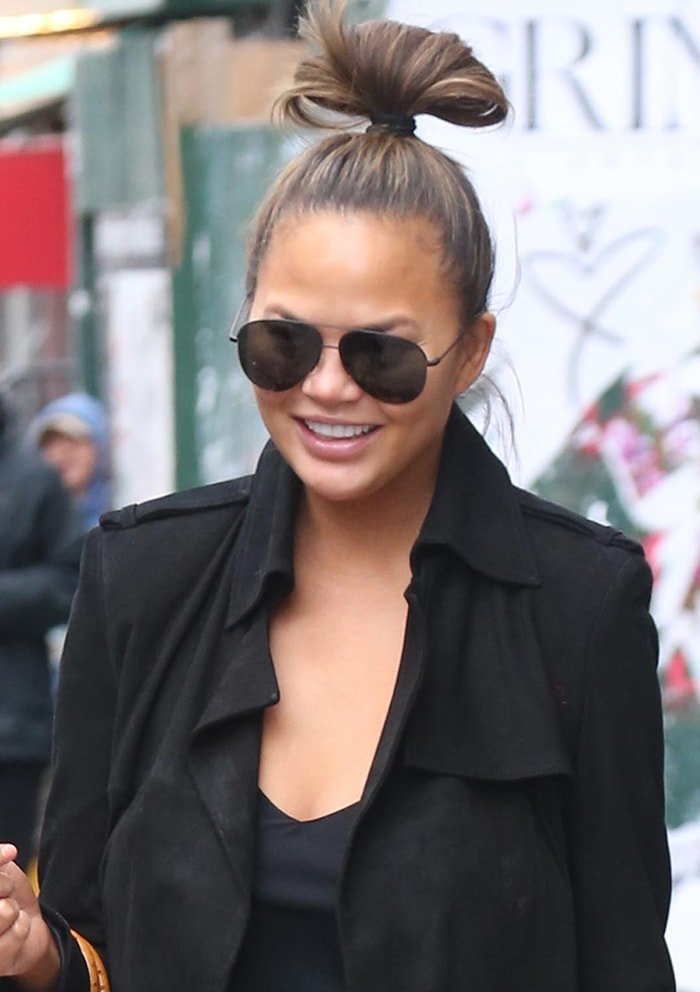 Chrissy Teigen keeps it simple with a messy bun and barely-there makeup