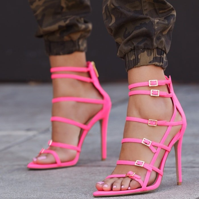 A strappy sandal featuring a stiletto heel, adjustable buckles, and back zipper closure