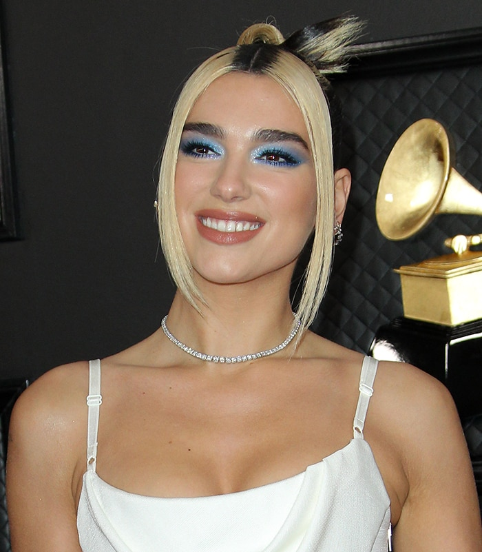 Dua Lipa wears '90s smokey blue eyeshadow and topknot hairstyle