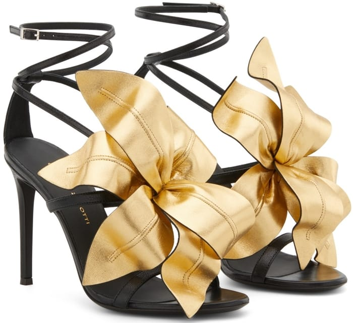 Black leather Lilium flower appliqué sandals from Giuseppe Zanotti featuring an open toe, a strappy design, a buckle fastening, a branded insole, a high stiletto heel and a contrasting gold-tone flower appliqué to the front