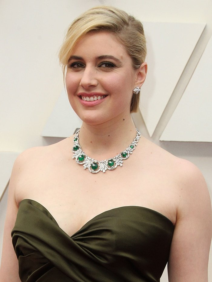 Greta Gerwig accessorizes with Bulgari jewelry and wears swept-back hairstyle and matching olive green eyeshadow