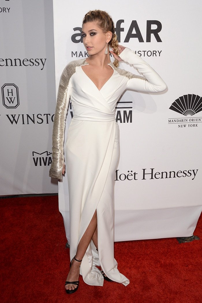 Hailey Baldwin in a white gown and a pair of black sandals at the 2016 amfAR New York Gala on February 10, 2016