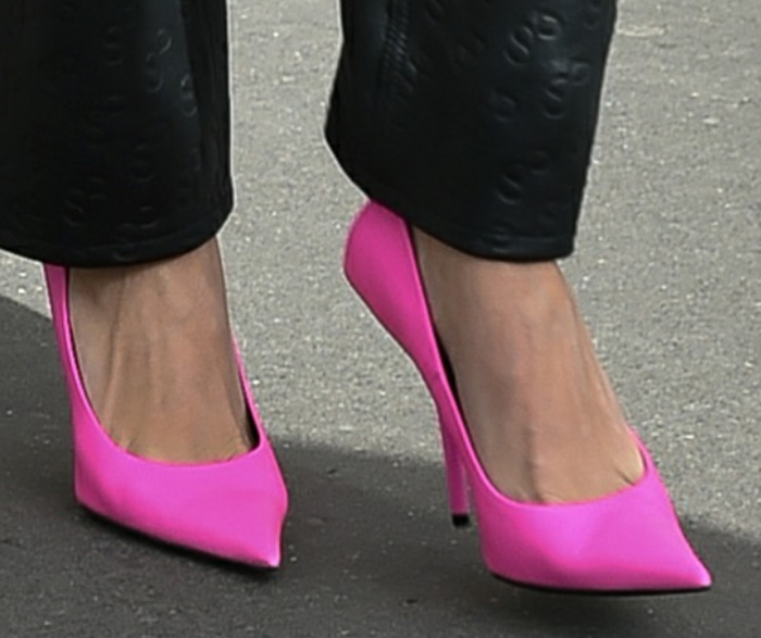 Hailey Bieber adds a pop of neon pink color to the look with Balenciaga pumps