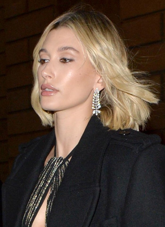 Hailey Bieber wears nude lip gloss and black mascara with tousled hairstyle
