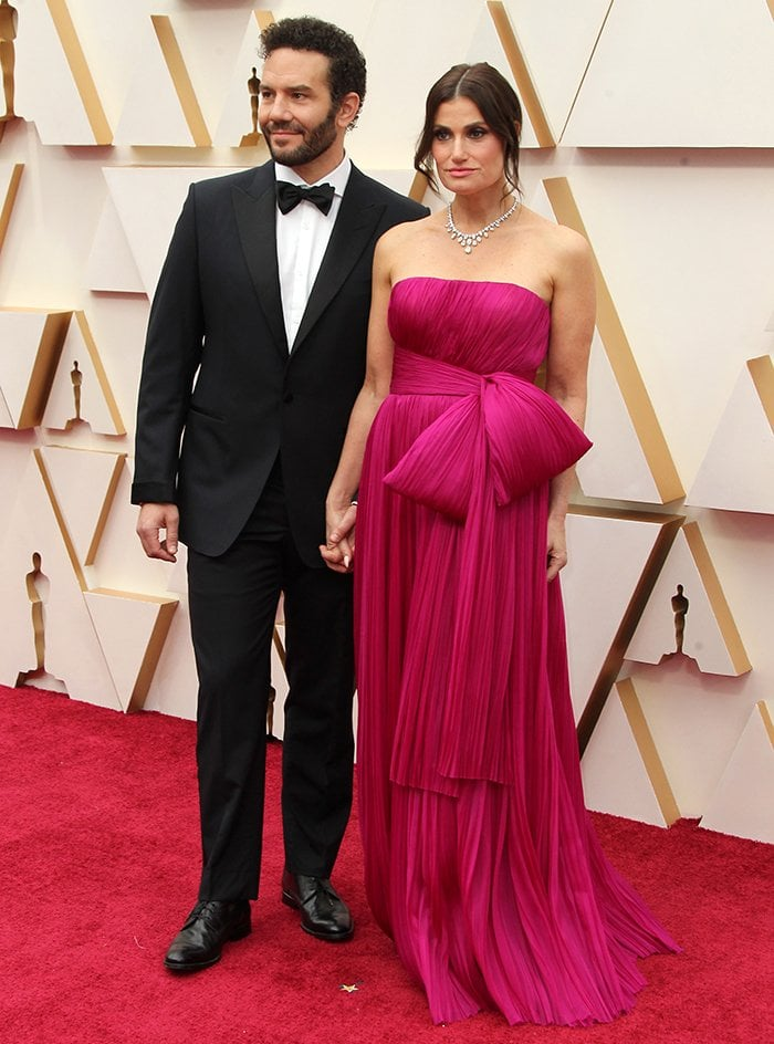 Aaron Lohr and Idina Menzel hold hands as they walk the 2020 Oscars red carpet in Los Angeles on February 9, 2020