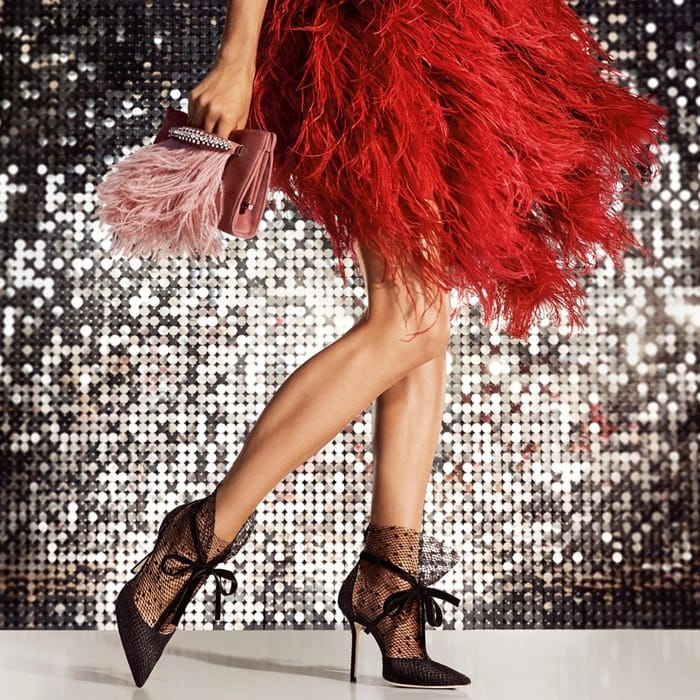 Jimmy Choo's plush suede pumps with sheer tulle overlay flocked with tiny polka-dots and velvet ribbon ties are pictured with a blush pink suede Venus clutch that is accented with feather trim and sparkling crystal embellishments