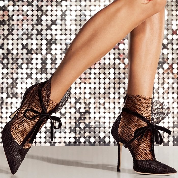 Take the socks-and-stilettos trend to daring new heights with this pointy-toe pump detailed with a fishnet stocking that flounces at the ankle