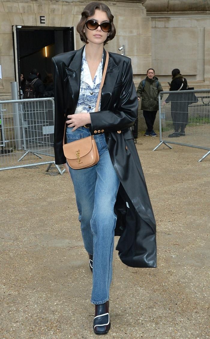 Kaia Gerber wearing a black Nanushka Manilla trench coat and denim jeans outside Chloe