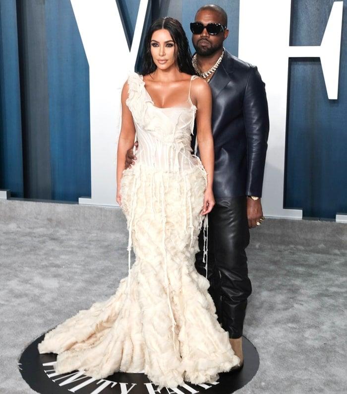 Kim Kardashian posing with her husband Kanye West at the 2020 Vanity Fair Oscar Party