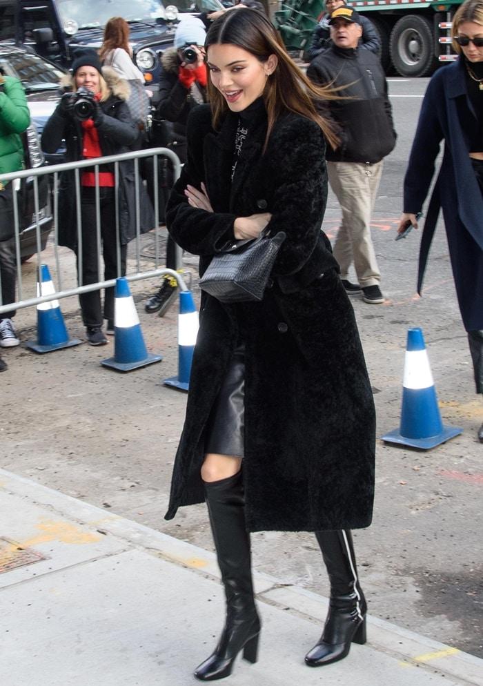 Kendall Jenner wears a Balenciaga coat in dyed lamb shearling fur outside Longchamp