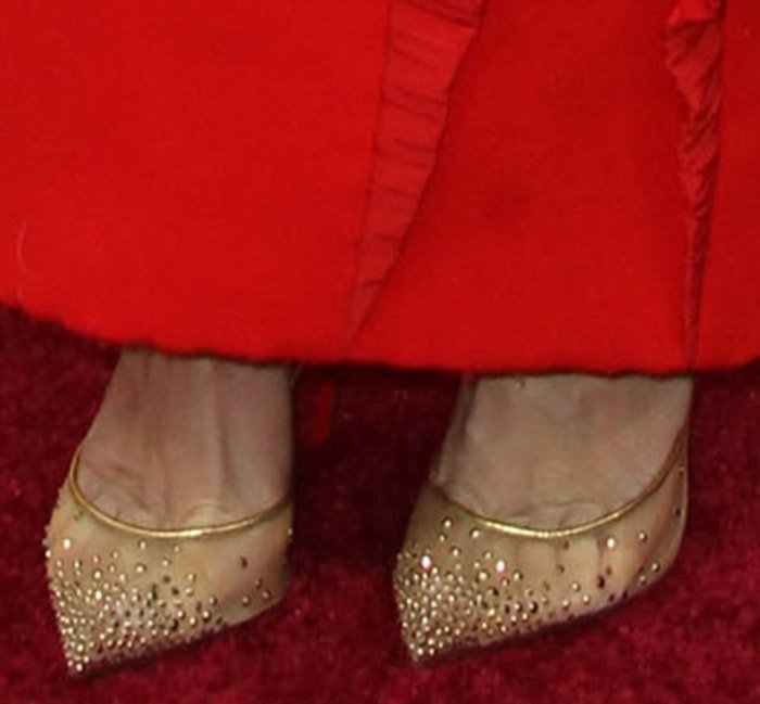 Kristen Wiig teams her quirky dress with Christian Louboutin gold mesh pumps