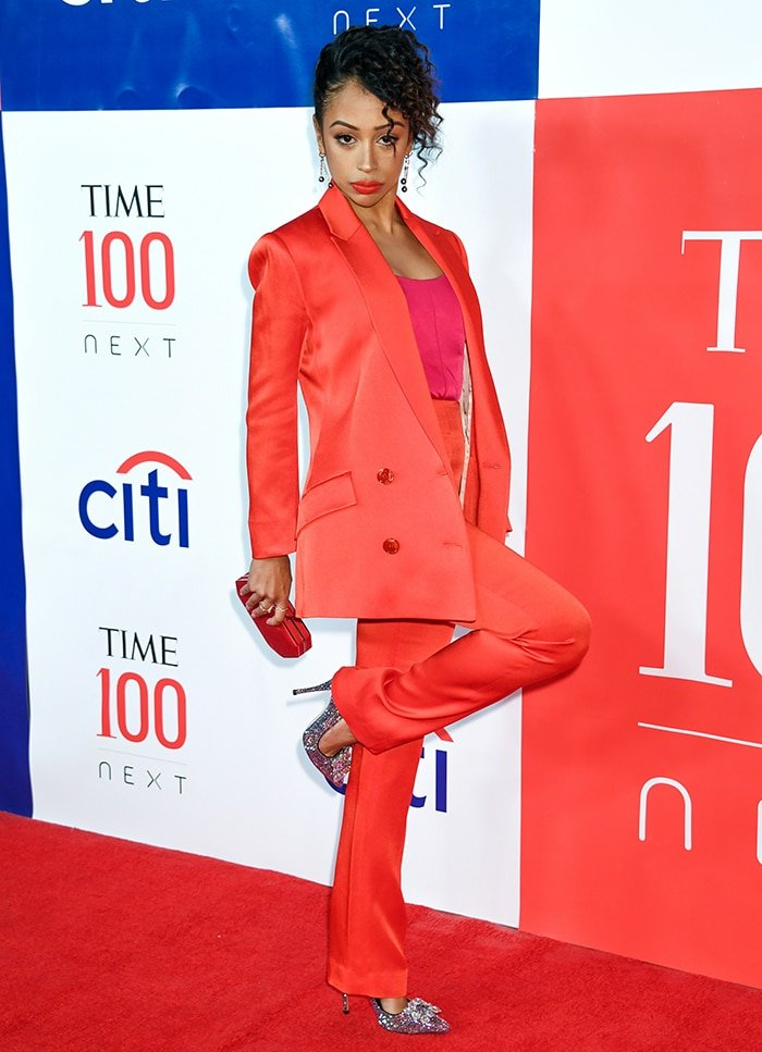Liza Koshy in a red pantsuit and glittery pumps at the Time 100 Next List red carpet