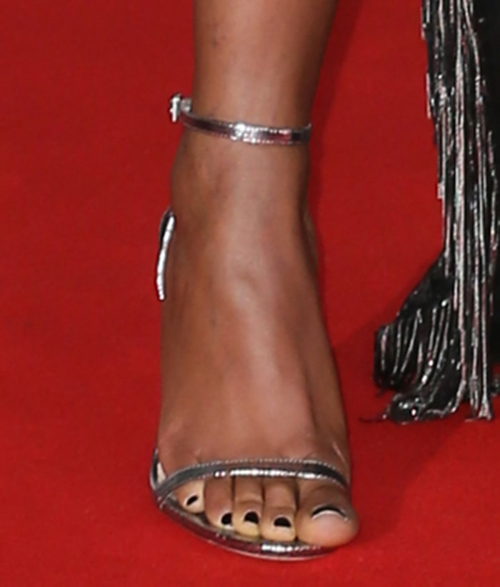 Naomie Harris slips her pedicured feet into a pair of silver sandals