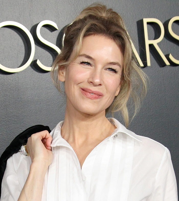 Renee Zellweger wears a messy high ponytail and barely-there makeup