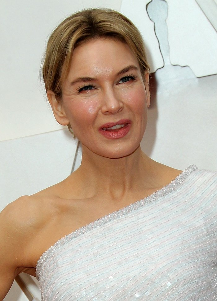 Renee Zellweger wears a chic center-parted updo and her signature soft pink makeup-look