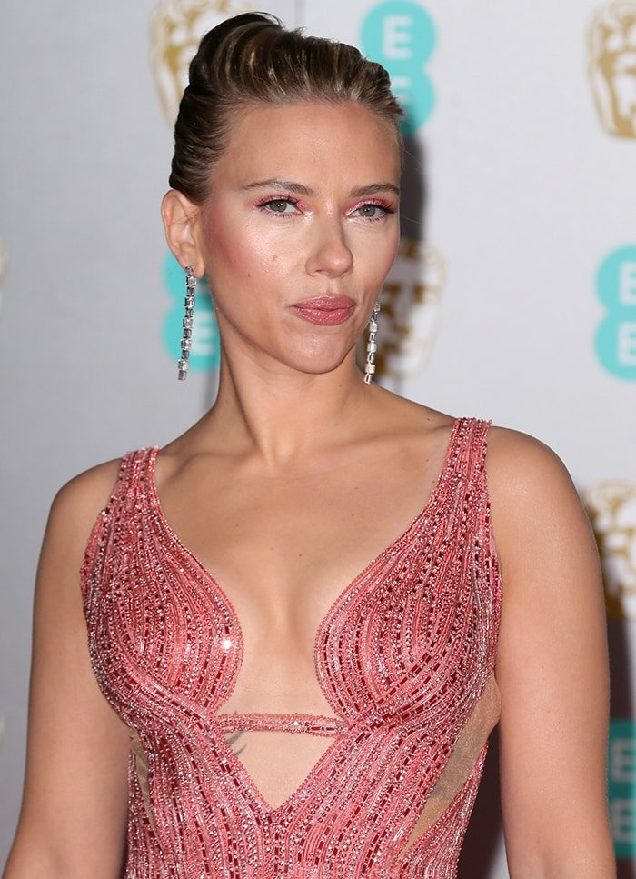 Scarlett Johansson wears a sleek chignon with pink eyeshadow, blush and lipstick