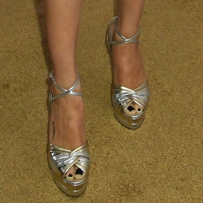 Selena Gomez has small black writing just along the right side of her right foot that reads sunshine