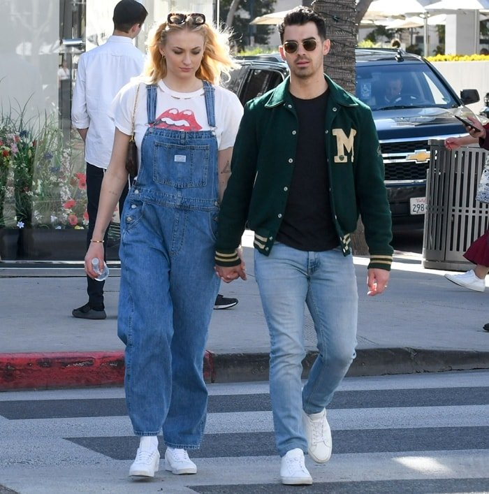 Sophie Turner rocks always-cool Levi's denim overalls featuring a comfy, slouchy fit and lightly faded wash