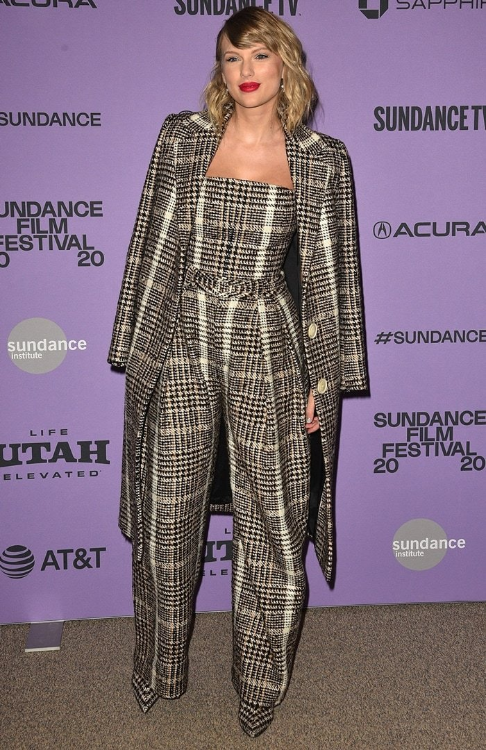 Taylor Swift wearing a checked single-breasted coat with a matching top, pants, and boots from Carmen March with Mateo jewelry to the premiere of her documentary Miss Americana