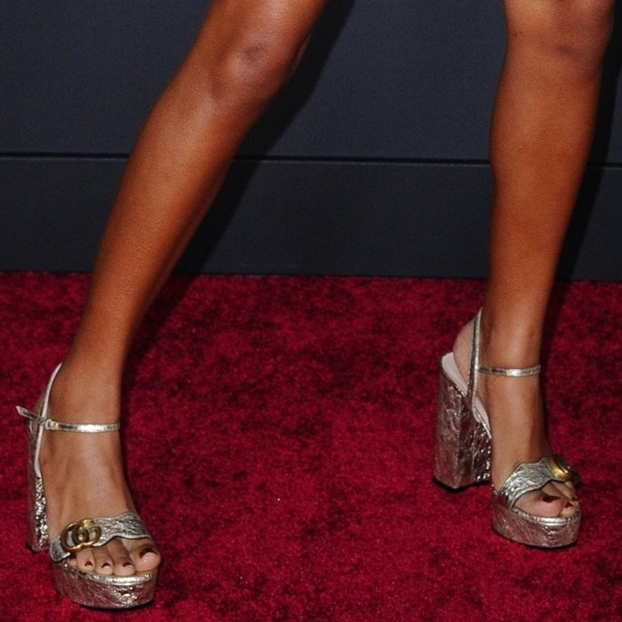 Yara Shahidi's pretty feet in gold-tone calf leather platform sandals featuring an open toe, a branded insole, a platform sole, a high block heel, a metallic sheen, a buckle fastening, and a double G appliqué