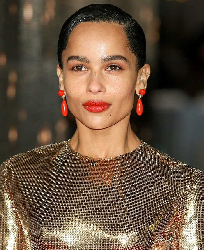 Zoe Kravitz teams her gold dress with coral earrings and lipstick