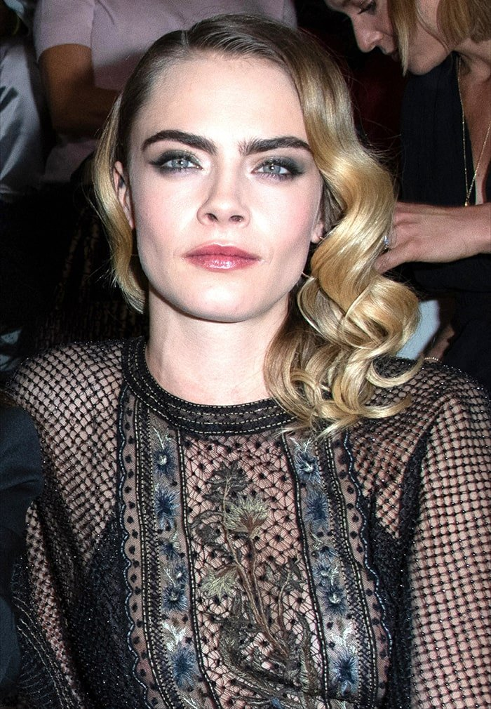 Cara Delevingne wears side-parted curls with bold brows, smoky eyeshadow and pink lipstick